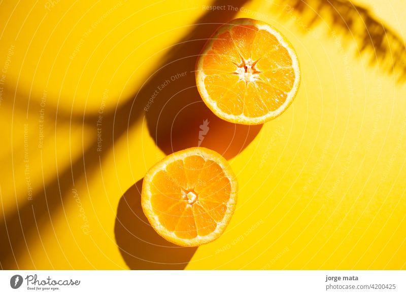 2 Orangen im Frühling mit gelbem Hintergrund Lebensmittel Frucht Frische saftig Vitamin Zellstoff frisch Farben Nährstoffversorgung Zitronensäure fruchtig
