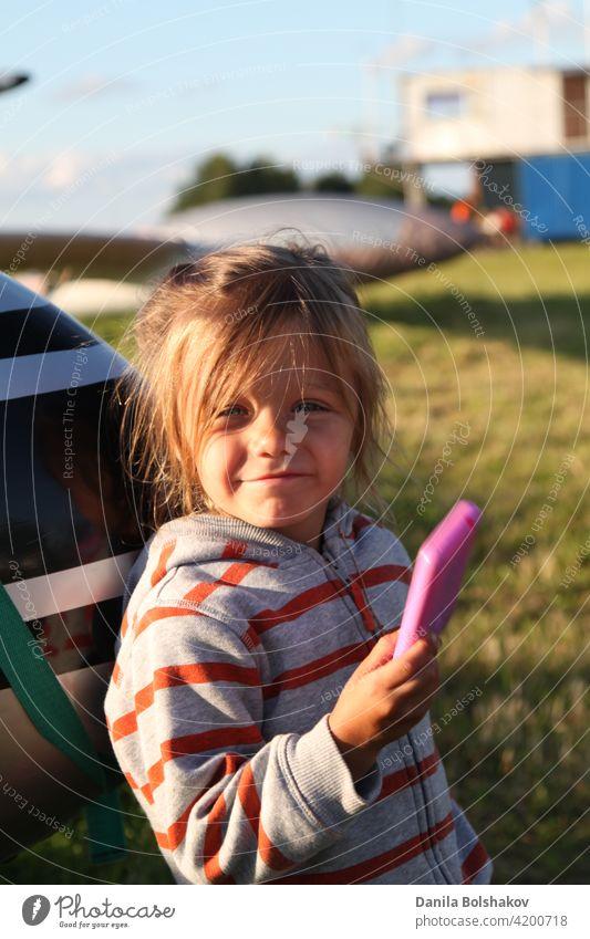 Kind spielt Fotograf im Freien. Mädchen stellt sich vor, Bilder auf rosa Plastikspielzeug Telefon zu nehmen Schönheit Lächeln Rasen Hobby Konzept genießen