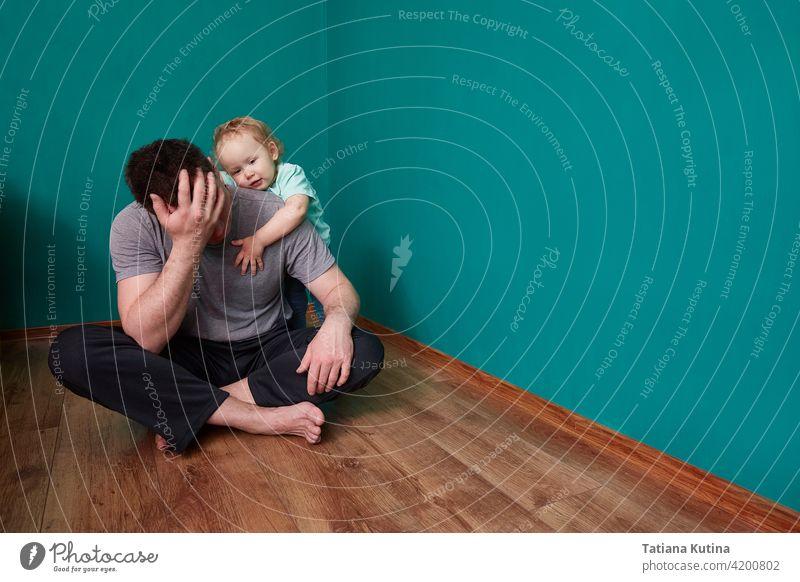 Das Kind hat Mitleid mit dem verstörten Vater, der in einem düsteren grünen Zimmer auf dem Boden sitzt. Mitleid haben psychische Belastung unglücklich