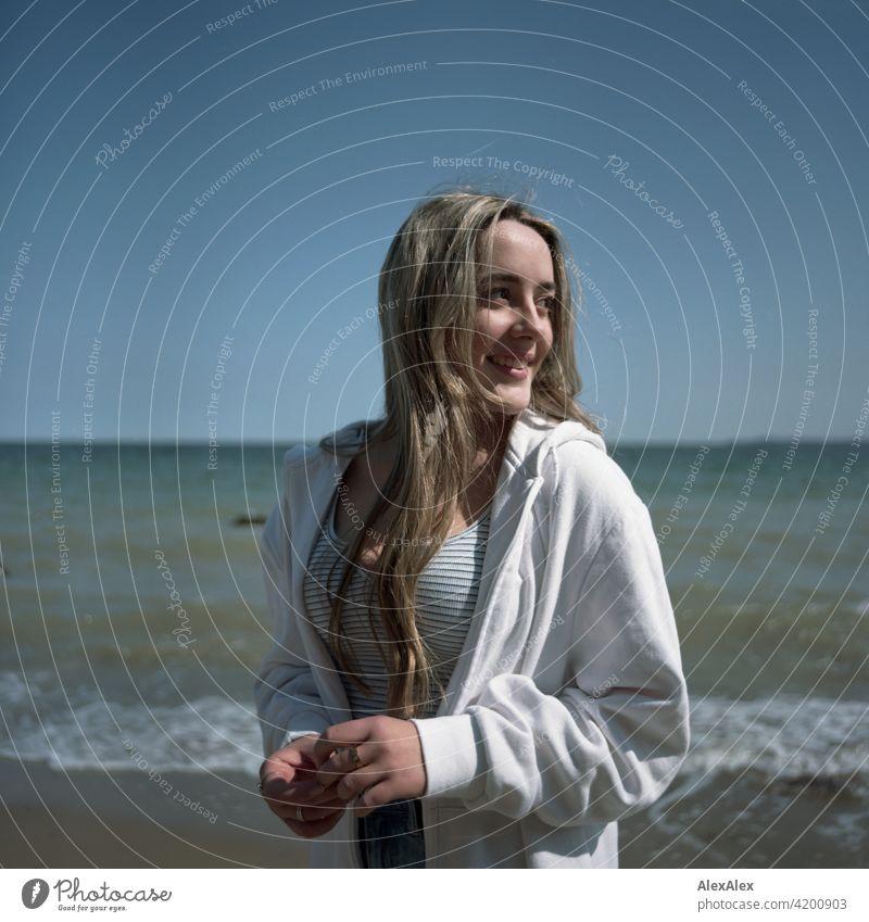 Analoges, rechteckiges Bild eines schönen blonden Mädchens das am Strand der Ostsee steht und  zur Seite schaut Lächeln freudig Landschaft durch Freude
