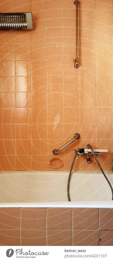 Altes Basezimmer in orange mit elektrischem Heizstrahler und Wasserhahn mit Duschkopf Badezimmer Fliesen u. Kacheln Häusliches Leben Badewanne Menschenleer