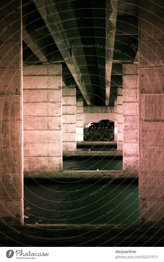 Eine außergewöhnliche Garage. Unter einer Brücke. Von der Sonne beleuchtet. Licht Architektur Schatten Wand Menschenleer Gebäude Außenaufnahme Mauer Kontrast
