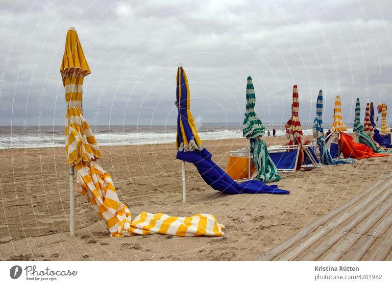 sonnenschirme am strand von trouville gestreift geschlossen sandstrand leer einsam verlassen liegestühle strandpromenade meer küste nebensaison nachsaison