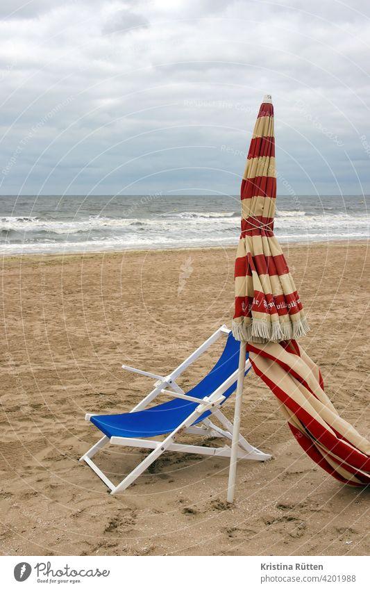 liegestuhl und sonnenschirm am strand von trouville gestreift geschlossen sandstrand leer einsam verlassen meer küste nebensaison nachsaison vorsaison
