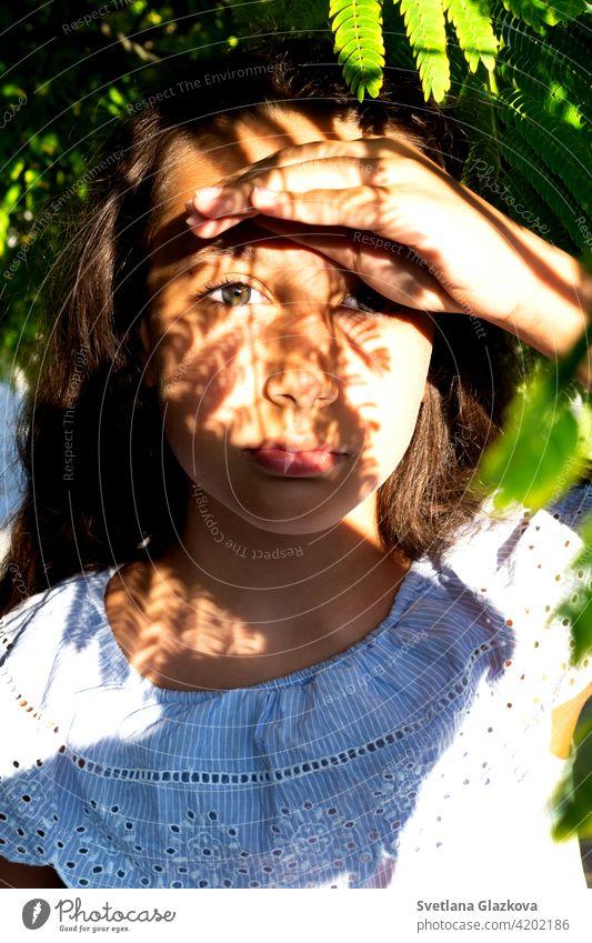 Spiel von Licht und Schatten Porträt eines schönen gebräunten kaukasischen niedlichen Mädchen in der tropischen Grünanlage. Reisen, Urlaub, warme Länder. Frau
