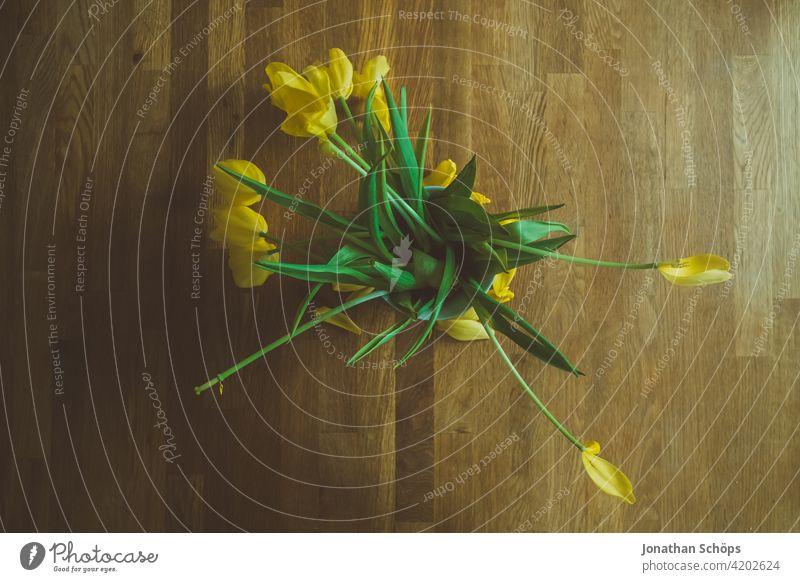 gelber Tulpenstrauß in Draufsicht auf Holztisch zum Muttertag Geschenk romantisch Pflanze grün Frühling Blumenstrauß schön Blüte Valentinshintergrund
