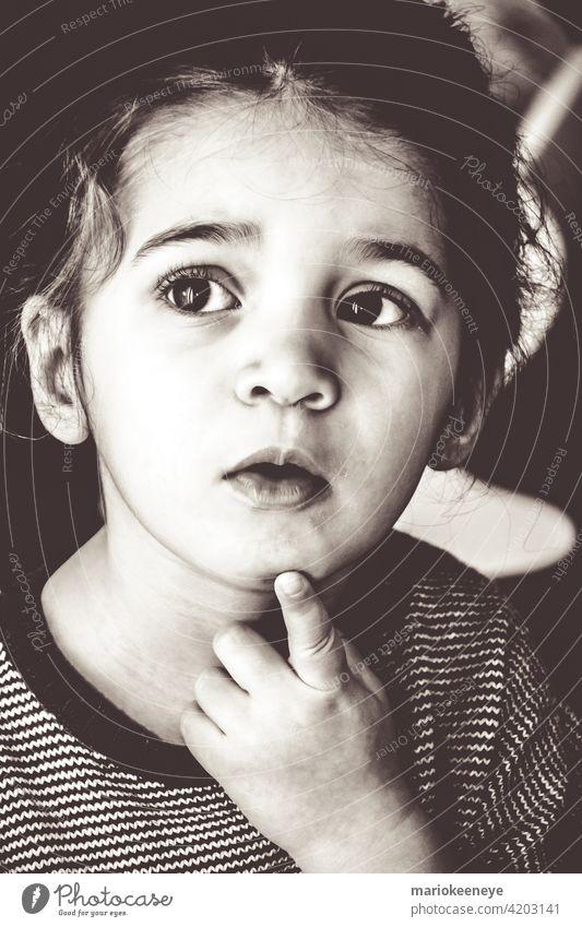 Schwarz-Weiß-Porträt eines kaukasischen kleinen Mädchens in einer nachdenklichen Haltung Individualität Unschuld schwarz auf weiß Gelassenheit Ruhe