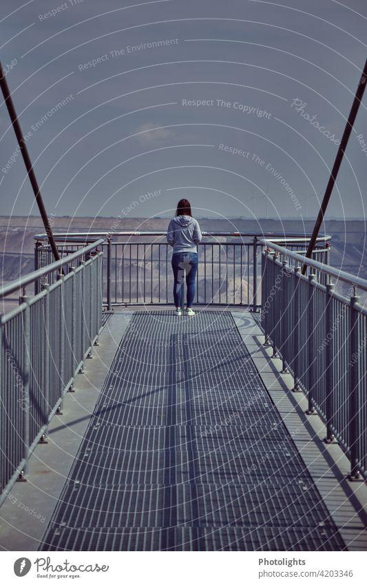 Junge Frau steht auf dem Skywalk am Aussichtspunkt Jackerath / Tagebau Garzweiler jung Haare grau Oberteil braun Sonne sonnig Erwachsene Mensch Außenaufnahme