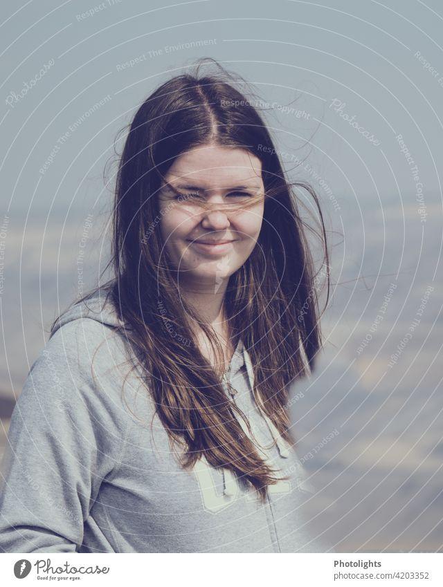 Porträt einer jungen Frau mit langen Haaren und grauem Oberteil braun Sonne sonnig Haare & Frisuren Erwachsene hübsch Mensch Lifestyle Portrait Außenaufnahme