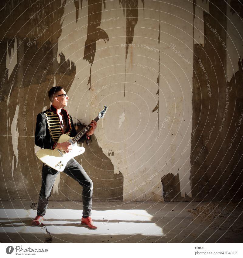 Saitenmeister Ganzkörperaufnahme Porträt maskulin Mann Musik Künstler Gitarre Musiker Mauer Wand Jacke Sonnenbrille lost places Ruine stehen Spielen kurzhaarig
