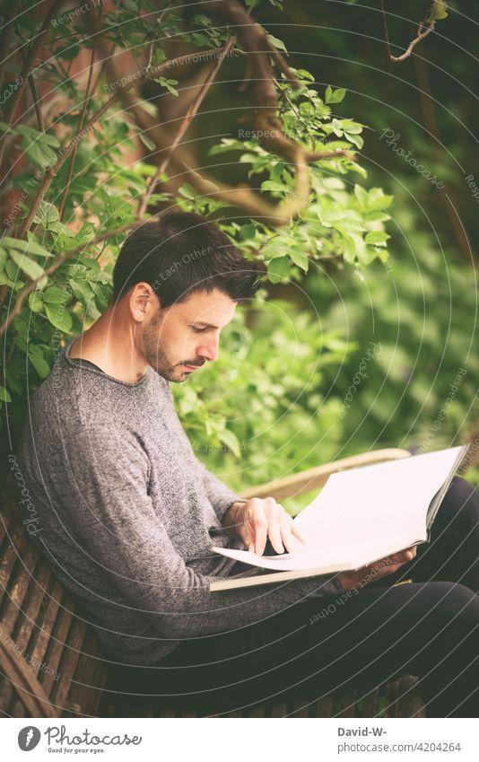 draußen in der Natur auf einer Bank ein Buch lesen Mann ruhe Bildung Leser Naturliebe