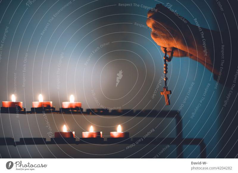 mit dem Rosenkranz im Gebet beten betend Kreuz Glaube & Religion Kerzen Kirche gedenken Hoffnung Hände Trauer Frau Gott Ruhe