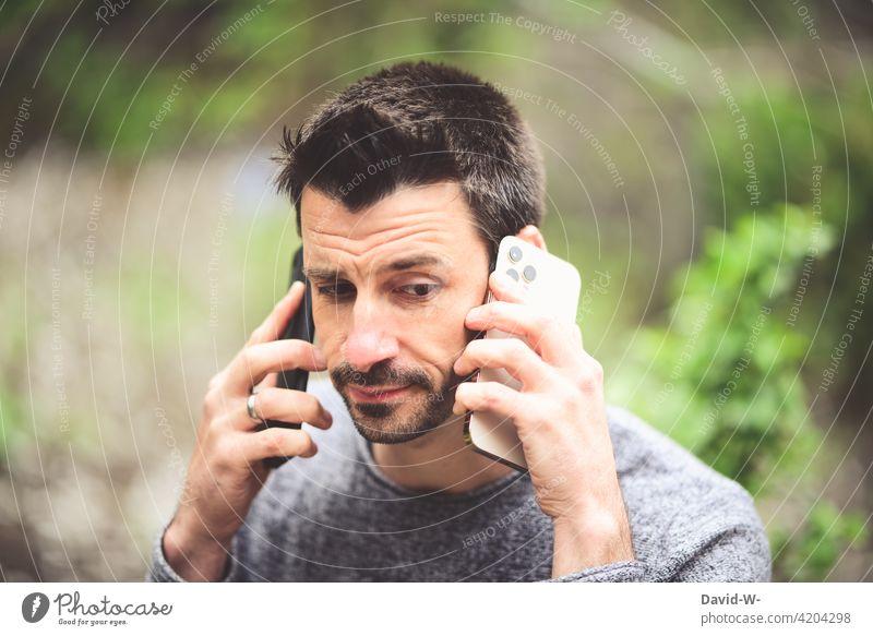 mit zwei Handys telefonieren - mulitasking multitasking Stress Mann Mobile Gespräch dual zuhören Erreichbarkeit