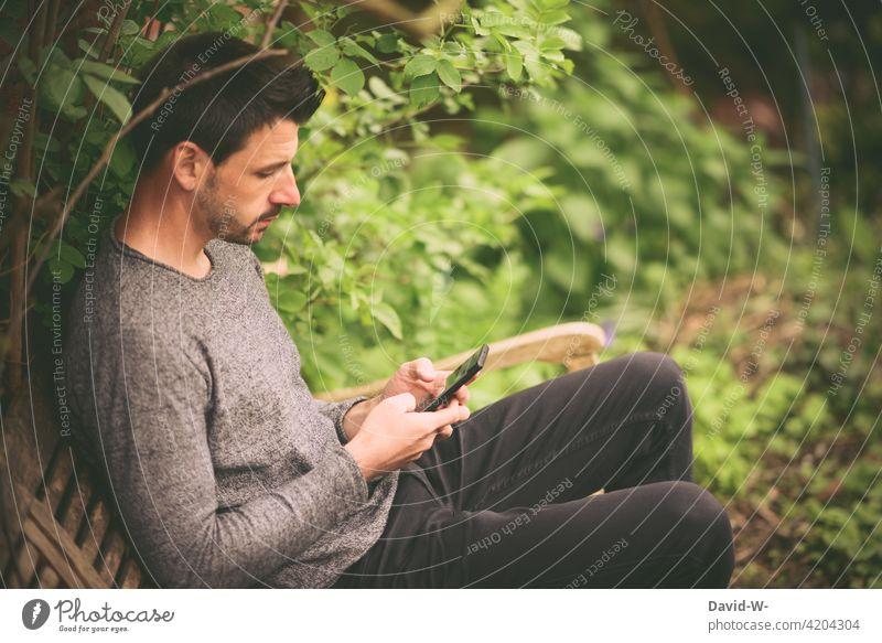 Handy in der Hand Mann Hände tippen draußen sitzen ruhe lesen vertieft online Lifestyle Smartphone
