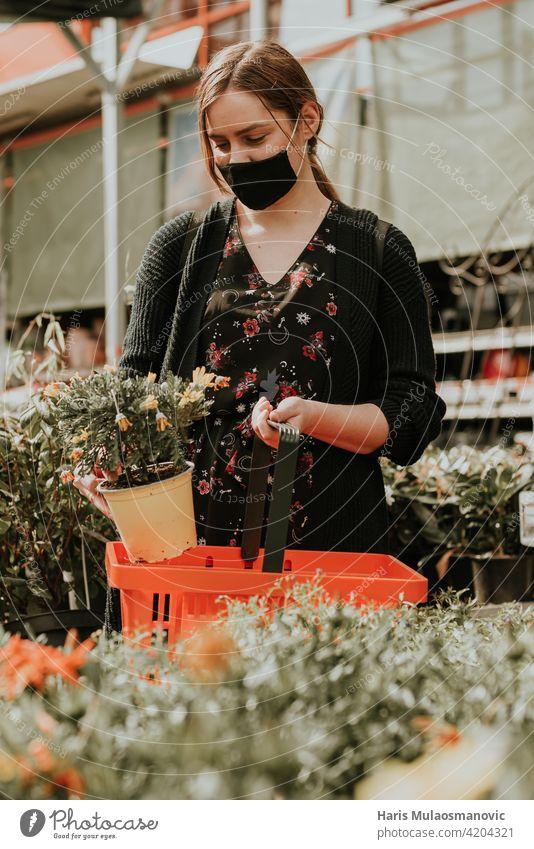Junge Frau kauft Blumen für den Garten schön Blüte kaufen Pflege Kaukasier Zentrum heiter Wahl auserwählend wählte Nahaufnahme farbenfroh wirtschaftlich