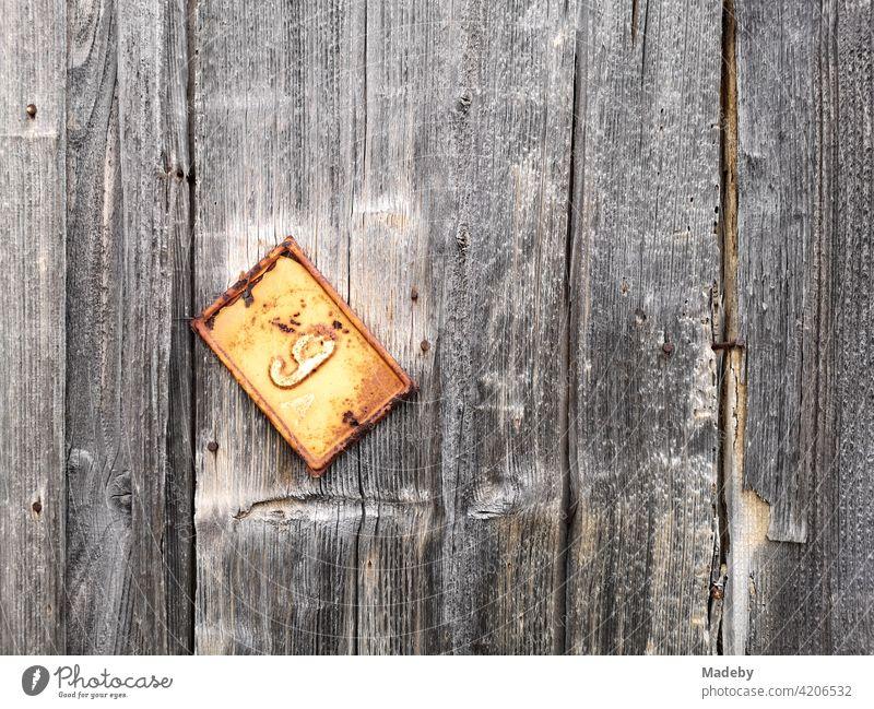Baumelndes rostiges Blechschild mit der Hausnummer an einer alten Bretterwand in der Altstadt von Alacati bei Cesme am Mittelmeer in de Provinz Izmir in der Türkei