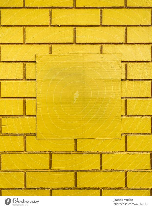 Gelbe Ziegelwand mit zentraler quadratischer Freifläche. gelb gelber Hintergrund Backsteinwand Wand gelbe Wand Textfreiraum Mitte Farbfoto Baustein