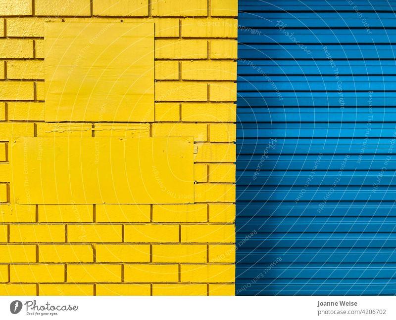 Gelbe Ziegelwand und blaues Rolltor. blau und gelb gelbe Wand blaue Tür Farbfoto Außenaufnahme Tag Metall Architektur Gebäude Eingang Bauwerk