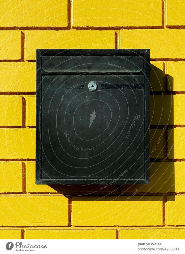 Gelbe Ziegelwand mit schwarzem Briefkasten. gelb gelbe Wand Backsteinwand Schatten bunt Außenaufnahme Tag tagsüber leuchtende Farben Baustein Farbfoto