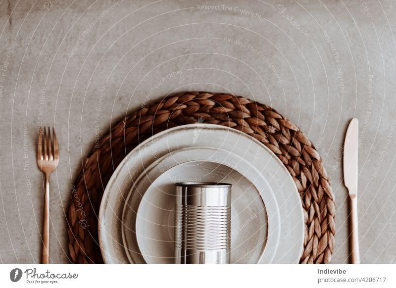 Dose von Lebensmitteln in einem Teller auf Rattan Esszimmermatte mit goldenen Besteck auf einem Tisch flach legen Mahlzeit Büchse flache Verlegung konservieren