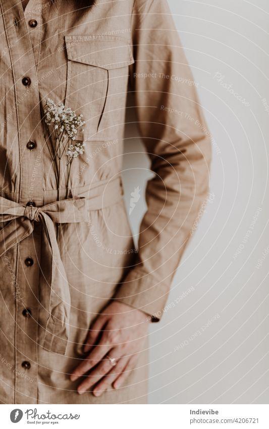 Frau in einem beigen Kleid mit Blume brünett Mode Lifestyle Herbst schön Blumenstrauß braun Konzept Handwerk Detailaufnahme trocknen Gerät gesichtslose Frau