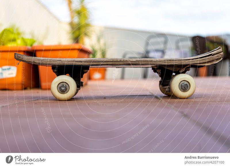 Blick auf ein altes Skateboard auf der Terrasse des Hauses. Selektiver Fokus Skateboarding extrem Beton Surfen Rad Ansicht Freizeit Seite Farbe hoch Genuss