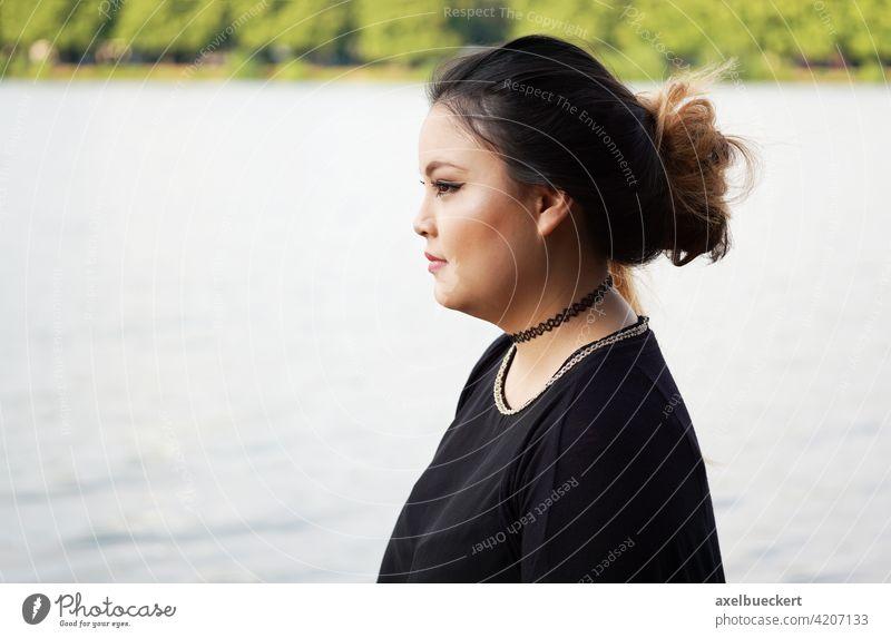 Profilansicht einer jungen asiatischen Frau am Wasser Asiate asiatin Junge Frau Fluss See Mädchen ernst Seite Einsamkeit allein einsam Blick nachdenken Denken