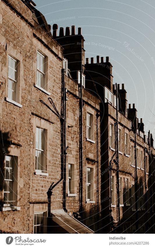 Straßenansicht von zusammengebauten Häusern. Backsteinmauer, Außenkanäle, weiße Fenster und Schornsteine an einem sonnigen Tag. Gebäude Architektur alt