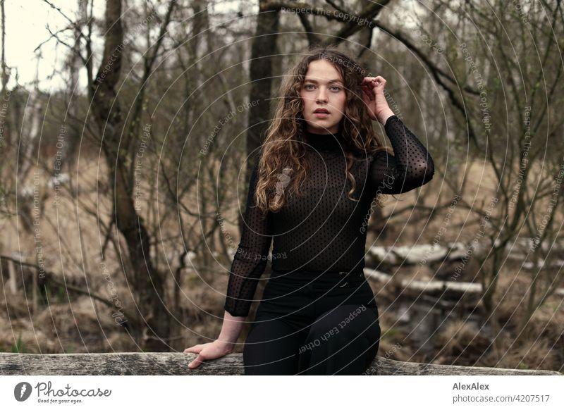 Portrait einer jungen Frau mit langem, brünettem, lockigem Haar vor einer Moorlandschaft auf einer Bank junge Frau 18-30 Jahre schön Schönheit Haare lange Haare