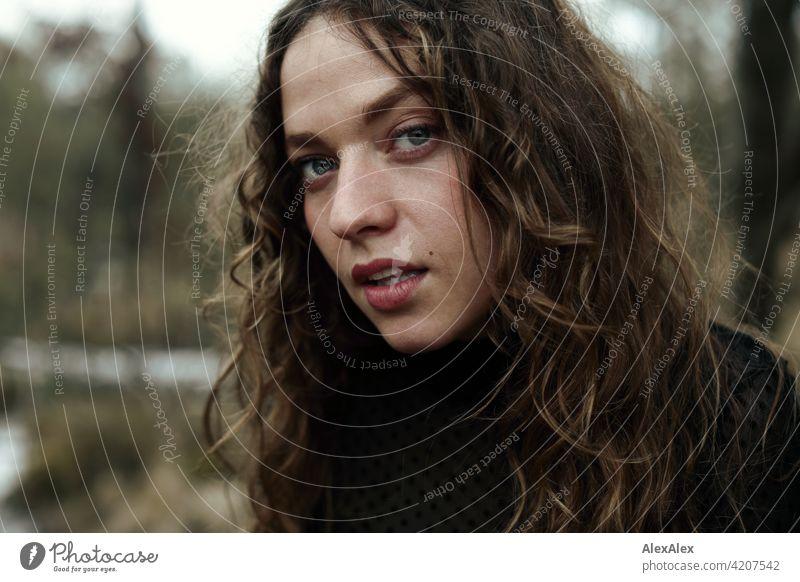 Portrait einer jungen Frau mit langem, brünettem, lockigem Haar vor einer Moorlandschaft junge Frau 18-30 Jahre schön Schönheit Haare lange Haare Locken