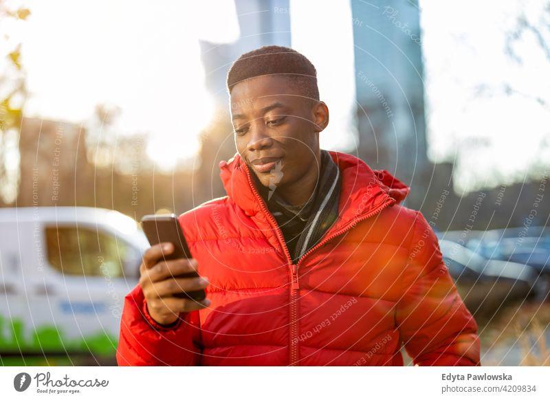 Junger Mann mit Smartphone im Freien in städtischer Umgebung schwarz außerhalb Straße urban tausendjährig Stehen Afrikanisch Großstadt Warschau eine