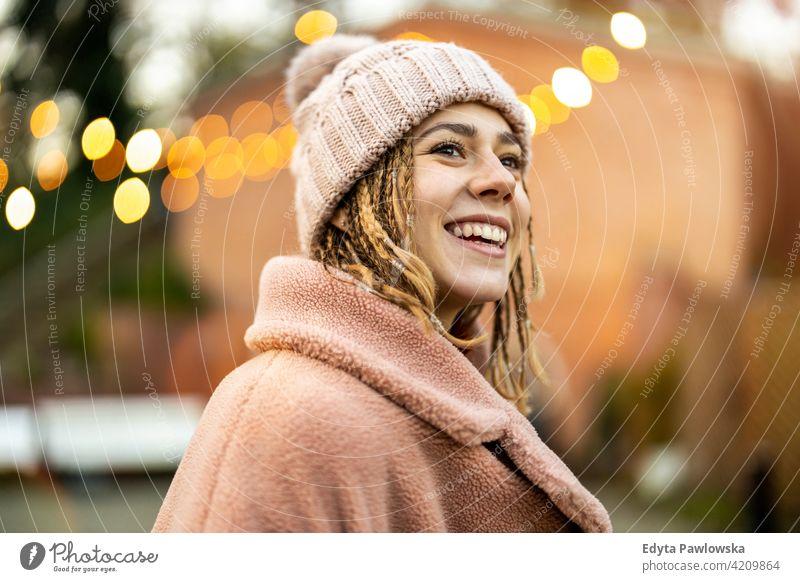 Verspielte junge Frau mit geflochtenem Haar im Freien tausendjährig auflehnen Behaarung Zopf urban Großstadt Straße Teenager trendy cool warme Kleidung Winter