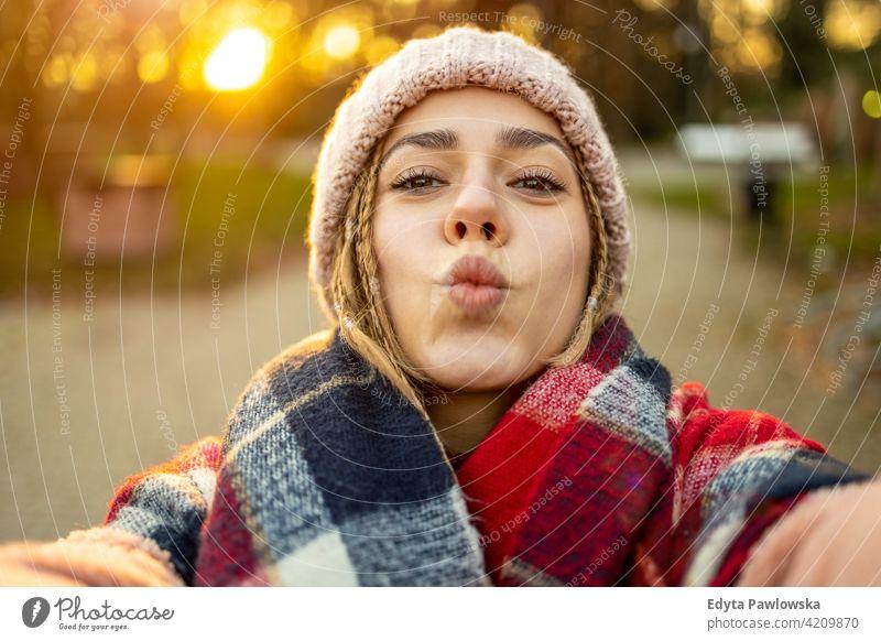 Selbstporträt einer verspielten jungen Frau im Freien tausendjährig auflehnen Behaarung Zopf urban Großstadt Straße Teenager trendy cool warme Kleidung Winter