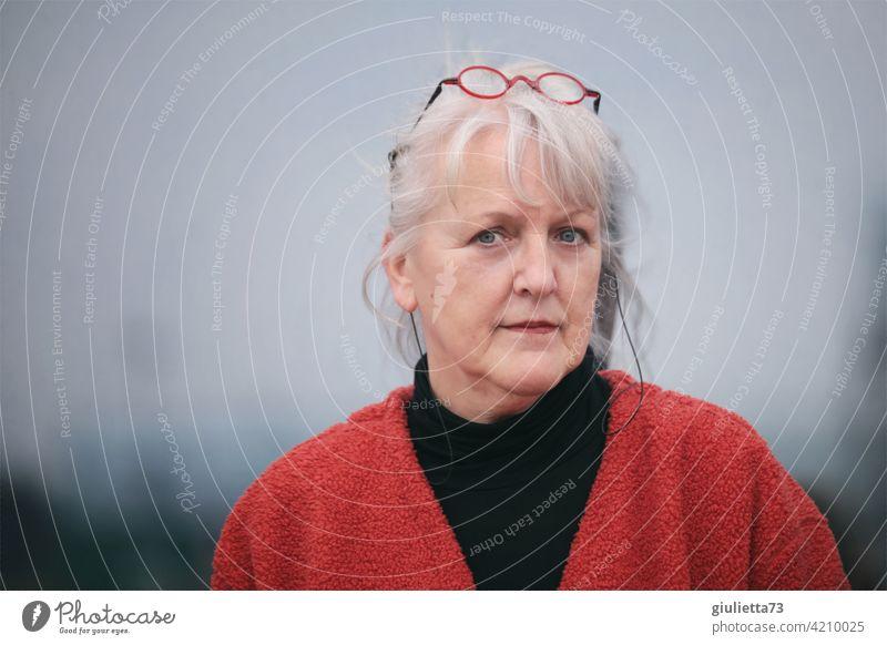 Porträt einer sympathischen, älteren Frau mit weißen Haaren und Brille auf dem Kopf Zentralperspektive Schwache Tiefenschärfe Unschärfe Schatten Licht Tag