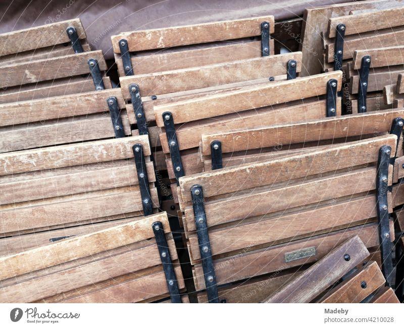 Zusammengeklappte Bistrostühle mit braunem Holz vor einem Bistro in den Gassen der Altstadt von Alacati bei Cesme am Ägäischen Meer in der Provinz Izmir in der Türkei