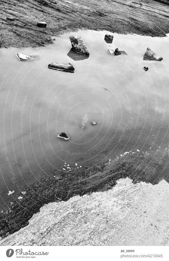 Am Wasser Pfütze Steine Schichten schwarz weiss Spiegelung Treibholz Ufer Reflexion & Spiegelung Himmel Menschenleer nass Außenaufnahme grau Schwarzweißfoto