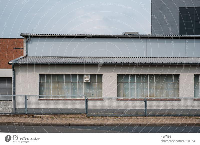 Lagerhalle mit Zaun und geschlossenen Fenstern trist wartezone 50ger Jahre Hafen Logistikbereich logistik Halle Schuppen Industrie Gebäude Fassade