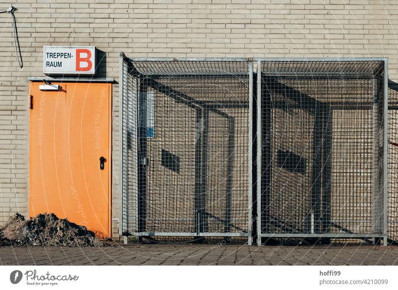 orange Tür zum Treppenhaus mit Gitterboxen auf einer Baustelle gitterbox Schattenwurf Zaun Barriere Metall Zugang Notausgang Fluchtweg Sicherheit Bauzaun