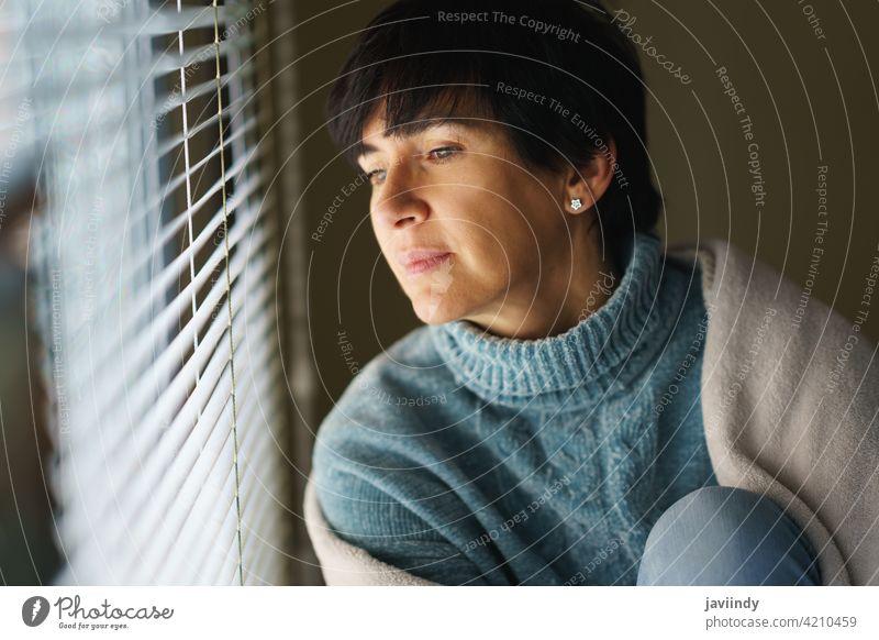 Glückliche Frau mittleren Alters mit nostalgischem Blick, während sie aus dem Fenster blickt. heimwärts 50s Nostalgie besinnlich nachdenklich Denken 40s Person