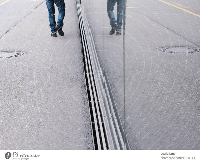 Ich und ich oder: ein Mann geht die Straße entlang. Beine, Jeans und schwarze Schuhe spiegeln sich in einem Schaufenster. alleine Spiegelung unterwegs
