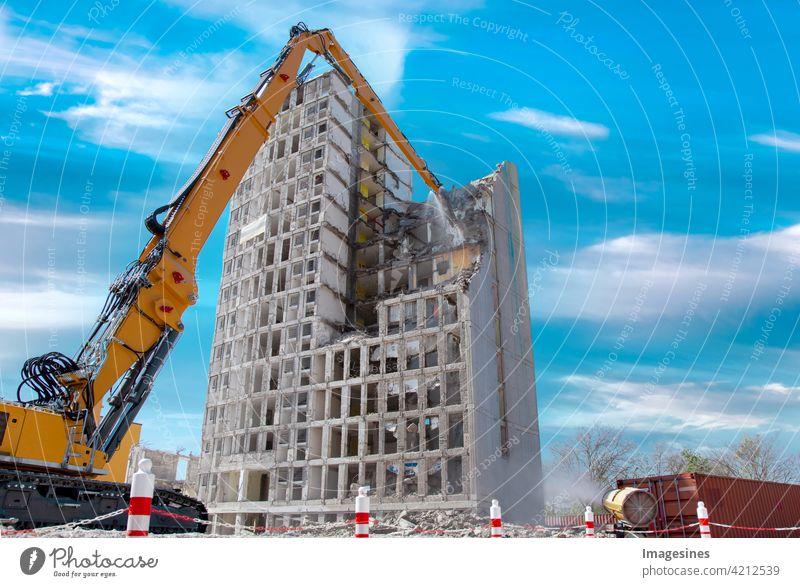 Abrisshaus. Kran wirft Wasser. Hochhausgebäude auf der Baustelle gegen blauen Wolkenhimmel. Abriss eines Hochhauses in der Innenstadt Gebäude Wohnung