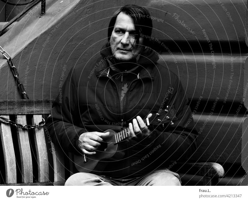 Ein Mann mit Ukulele Gesicht Porträt Winter Bank Sitzbank ernsthaft konzentriert Künstler Musiker Corona Für willma: die Bank bei Bäcker Willi. sensibel