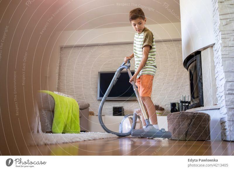 Junge staubsaugt Boden zu Hause Staubsauger Stock Staubsaugen Hausarbeit Hausarbeiten Hilfe Lernen Familie Menschen Kind Sohn Kinder Lifestyle elementar