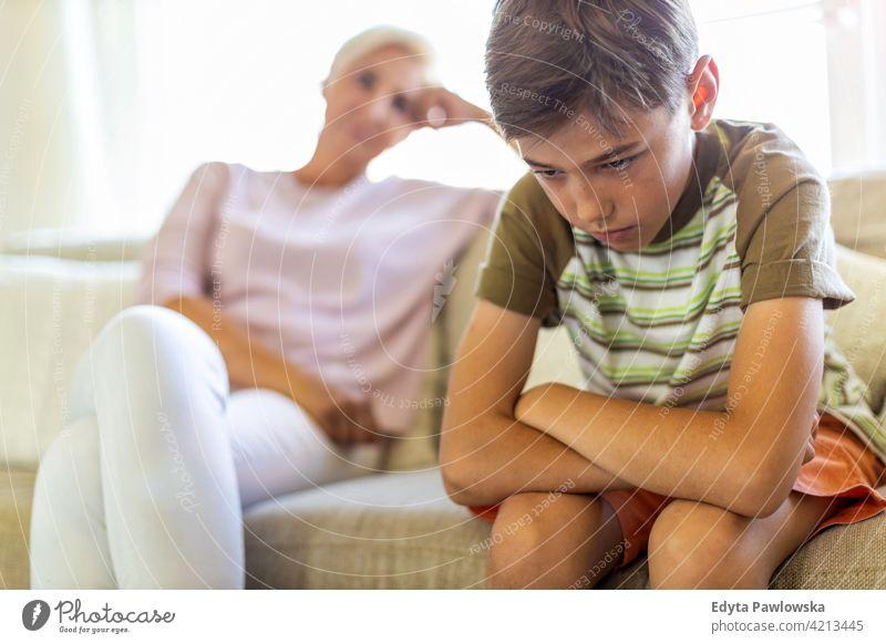 Wütender Junge und frustrierte Mutter sitzen auf dem Sofa verärgert argumentieren wütend Problematik Teenager Konflikt argumentierend ernst Einstellung Kind