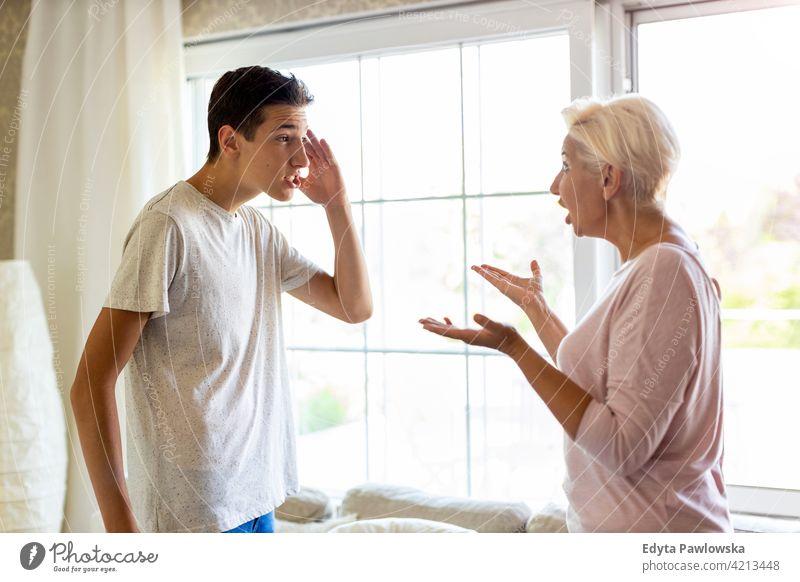 Mutter und ihr jugendlicher Sohn streiten sich zu Hause verärgert argumentieren wütend Problematik Teenager Konflikt argumentierend ernst Einstellung Kind Junge