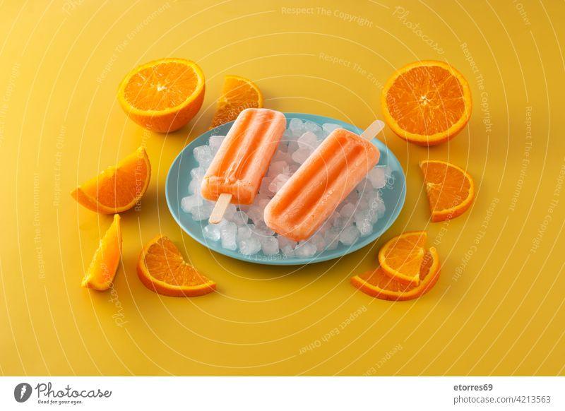 Orange Eis am Stiel auf blauem Teller Hintergrund Kuchen kalt farbenfroh cool Sahne Dessert Geschmack Lebensmittel frisch frostig gefroren Frucht selbstgemacht