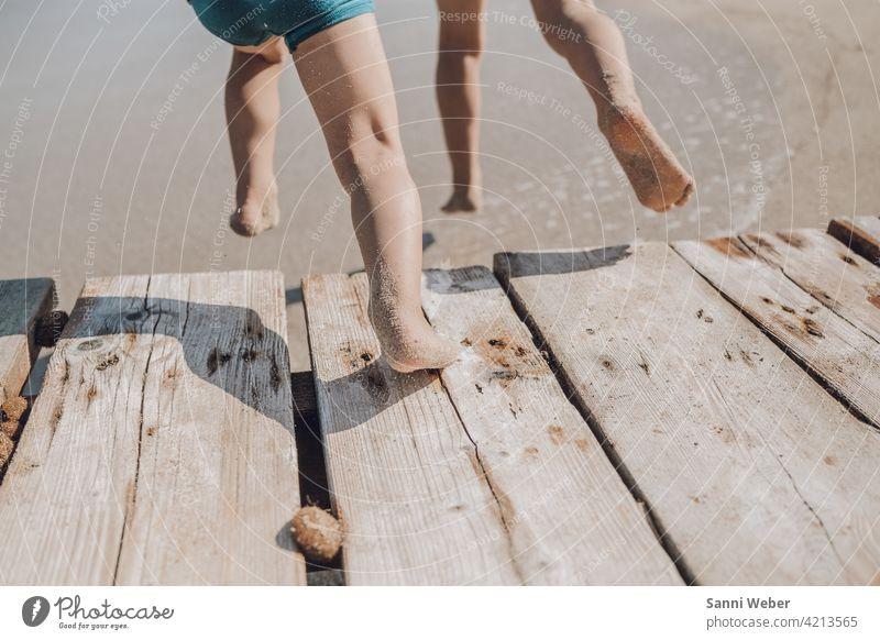 Kinder springen vom Steg ins Wasser Kindheit Spielen kinder Freude Natur Strand Fröhlichkeit Glück Außenaufnahme Farbfoto Ferien & Urlaub & Reisen fuesse