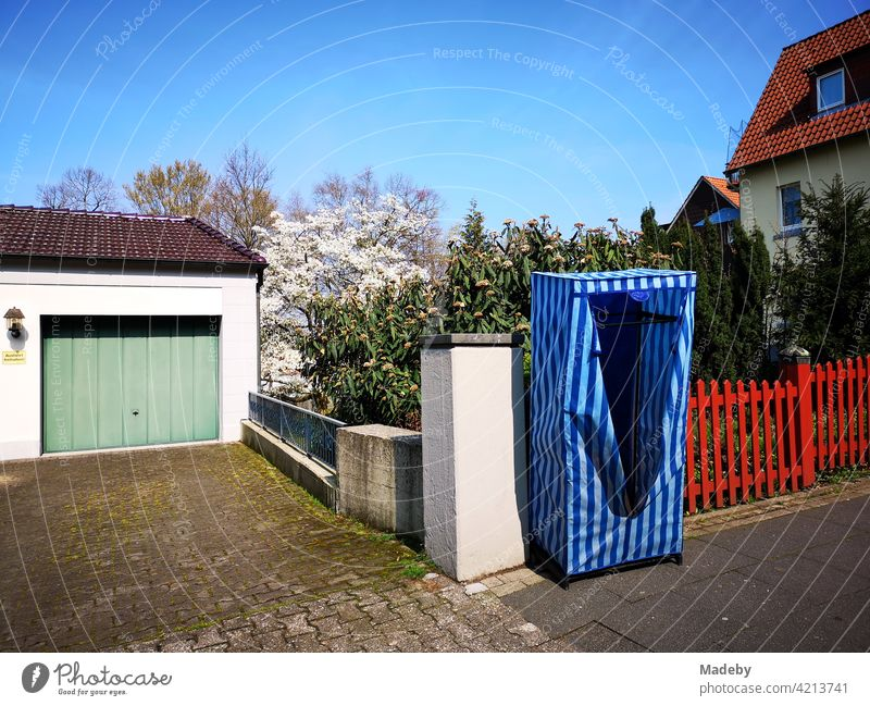 Mobiler blauer Kleiderschrank mit Streifen und Reißverschluss vor rotem Zaun auf dem Bürgersteig in Oerlinghausen bei Bielefeld am Hermannsweg im Teutoburger Wald in Ostwestfalen-Lippe