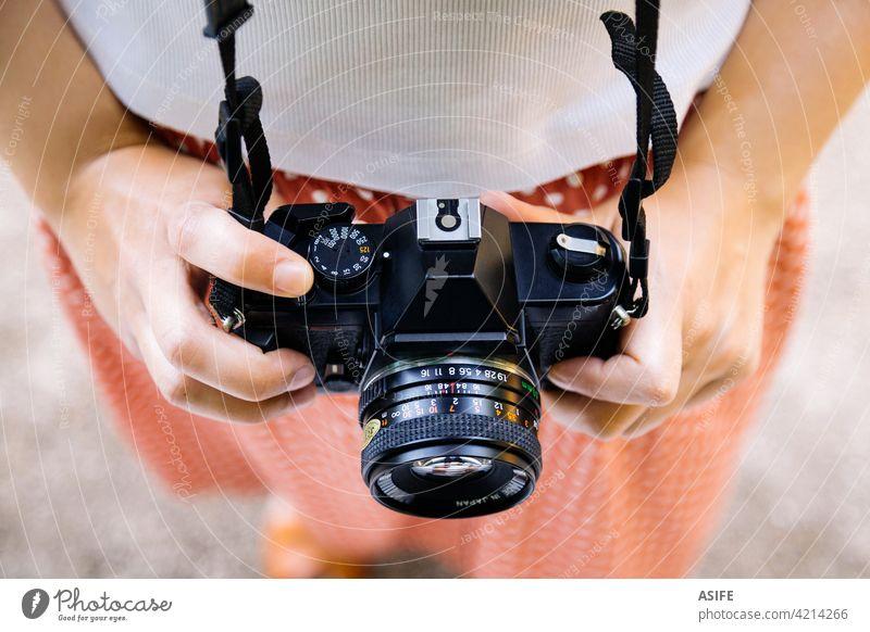Junge Frau Hände halten eine Retro-Fotokamera retro Fotograf Fotografie fotografisch Filmmaterial SLR jung Beteiligung Sommer im Freien Park unter Spaß reisen