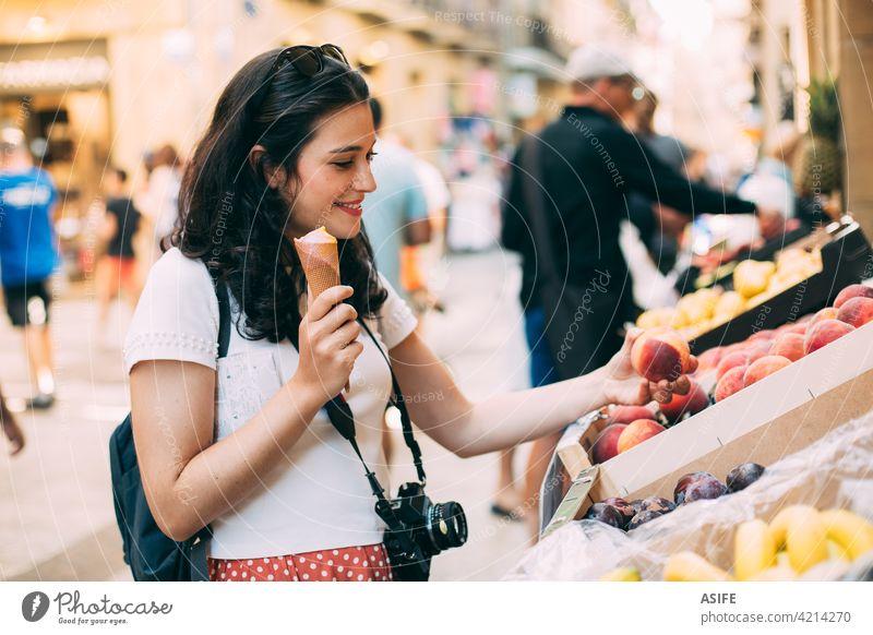 Junge touristische Frau isst ein Eis und kauft einige Früchte in einem Straßenmarkt Tourist kaufen Markt Lebensmittelgeschäft Frucht Urlaub reisen Feiertag